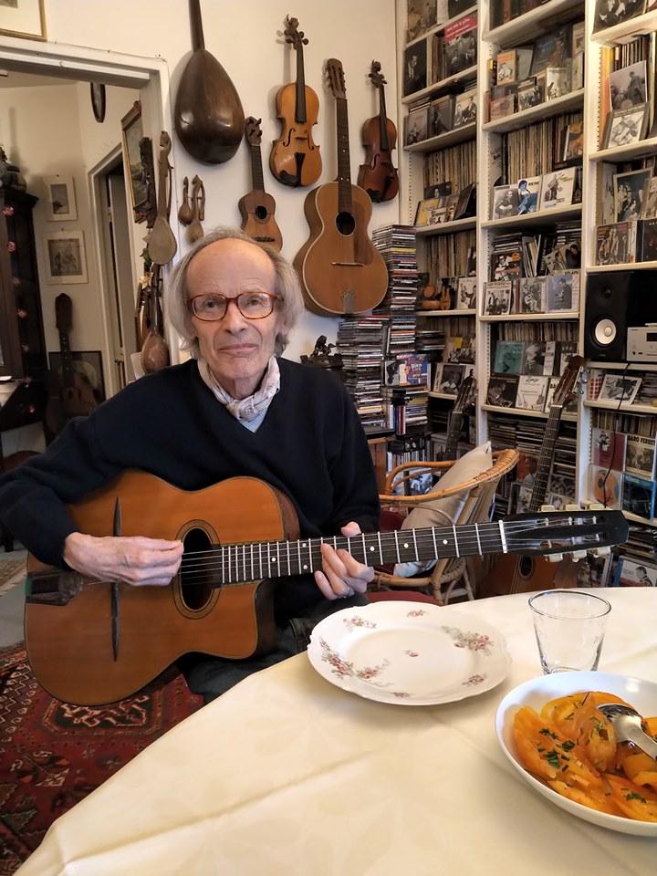 Alain Antonietto jouant de la guitare dans un appartement